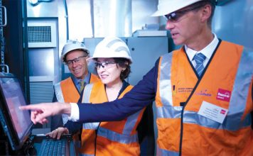 Steven Neave with Victorian Minister of Energy Lily D'Ambrosio and Buninyong local member Geoff Howard working on the controls on Powercor's battery unit